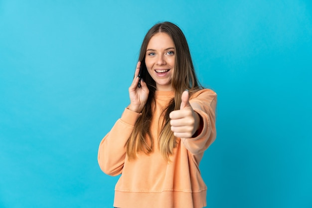 Giovane donna lituana isolata sulla parete blu mantenendo una conversazione con il cellulare mentre fa i pollici in su