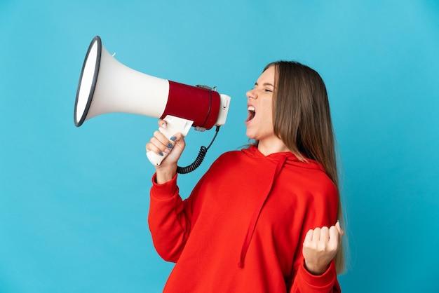 Giovane donna lituana isolata sulla parete blu che grida tramite un megafono per annunciare qualcosa in posizione laterale