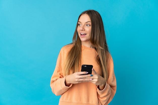 Giovane donna lituana isolata sulla parete blu utilizzando il telefono cellulare e alzando lo sguardo