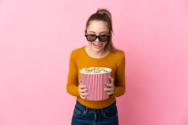 Giovane donna lituana isolata sulla parete rosa con gli occhiali 3d e che tiene un grande secchio di popcorn
