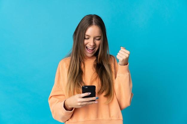 Giovane donna lituana isolata utilizzando il telefono cellulare e facendo il gesto di vittoria