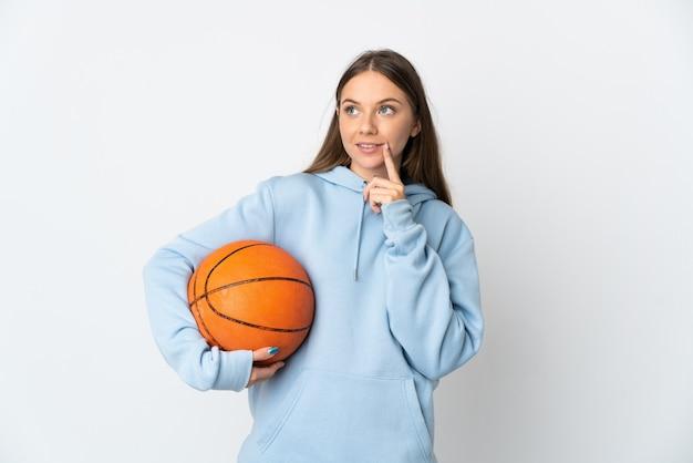 Giovane donna lituana che gioca a basket isolato su sfondo bianco pensando un'idea mentre guarda in alto