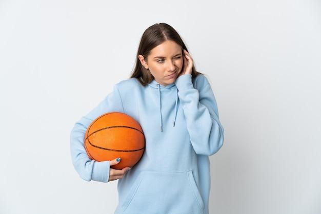 Giovane donna lituana che gioca a basket isolato sul muro bianco frustrato e che copre le orecchie