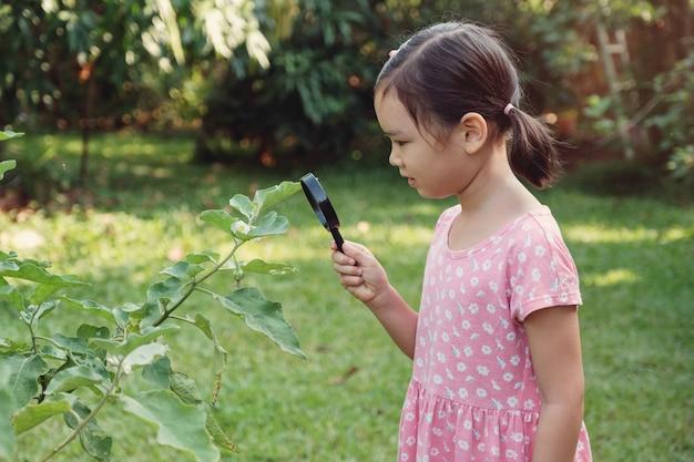 Giovane piccola ragazza asiatica guardando foglie attraverso una lente di ingrandimento