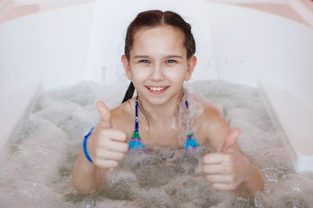La giovane ragazza adolescente carina è seduta nella vasca idromassaggio terapeutica e dà il pollice in su alla telecamera.