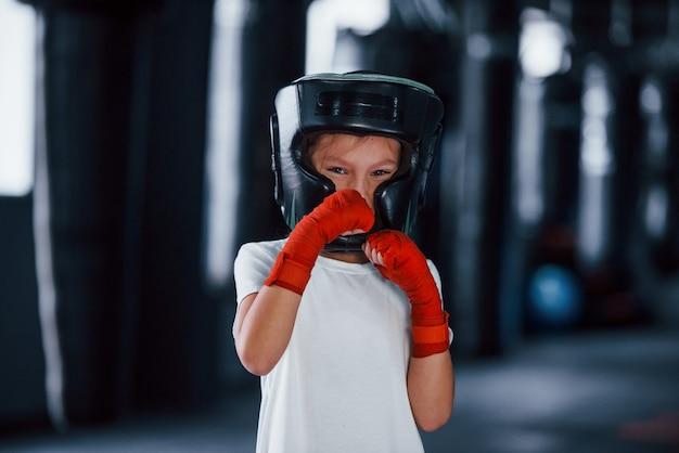 La giovane bambina in abbigliamento sportivo e cappello protettivo è in palestra ha una giornata di esercizio. concezione della boxe.