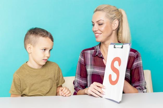 Giovane piccolo scolaro che fa i compiti con la madre