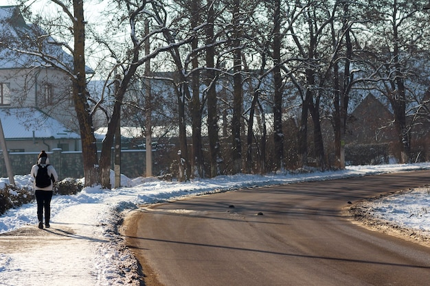 Giovane persona sola che cammina sulla vecchia strada vuota.