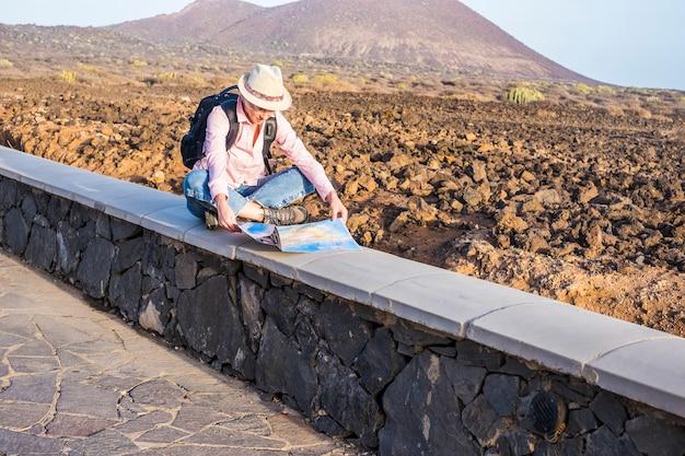Viaggiatore selvaggio giovane donna sola seduto e guardando la mappa per l'aereo di viaggio con deserto e montagne