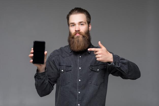 Il giovane uomo barbuto lungo ha indicato il grido della macchina fotografica del telefono isolato su spazio grigio