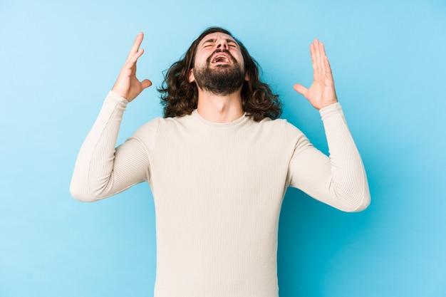 Uomo giovane capelli lunghi isolato su uno sfondo blu che grida al cielo, alzando lo sguardo, frustrato.