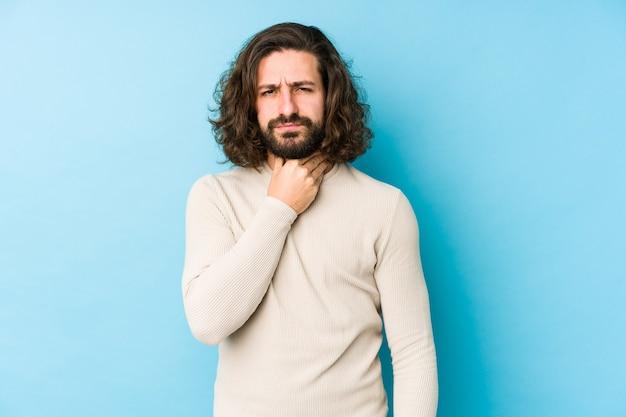 Il giovane uomo con i capelli lunghi isolato su una parete blu soffre di dolore alla gola a causa di un virus o di un'infezione.