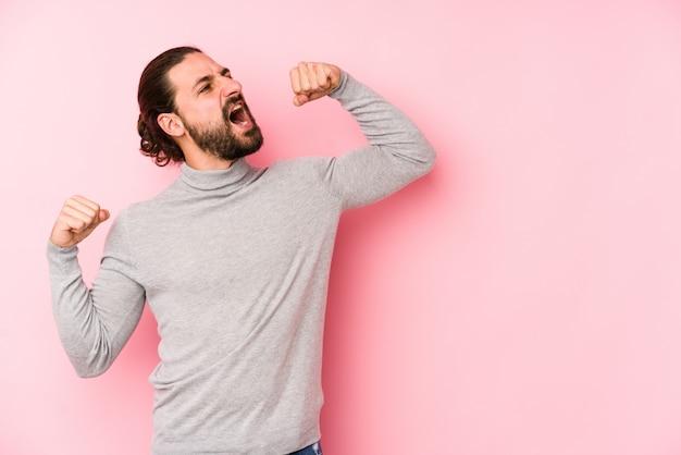 Uomo giovane capelli lunghi isolato su un muro rosa alzando il pugno dopo una vittoria