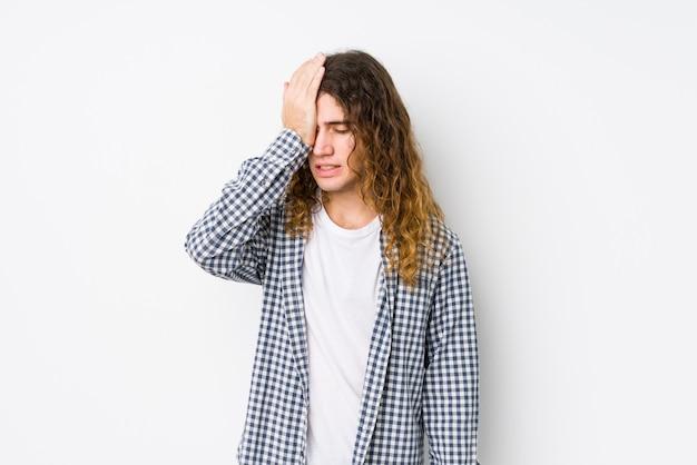 Giovane uomo capelli lunghi in posa isolato dimenticando qualcosa, schiaffi sulla fronte con il palmo e chiudendo gli occhi.
