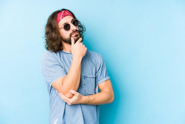 L'uomo giovane dei capelli lunghi che indossa un sembrare dei pantaloni a vita bassa di festival ha isolato lo sguardo lateralmente con l'espressione dubbiosa e scettica.