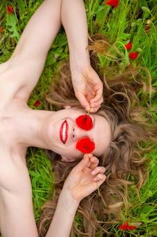 Una giovane ragazza dai capelli lunghi gode dei colori della natura su un campo di papaveri in fiore in una calda giornata estiva.