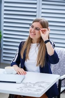 Giovane donna dai capelli lunghi che lavora con un computer portatile, seduta su una terrazza all'aperto in un caffè. concetto di sviluppo del business, ragazza in pausa pranzo che lavora davanti a una tazza di caffè