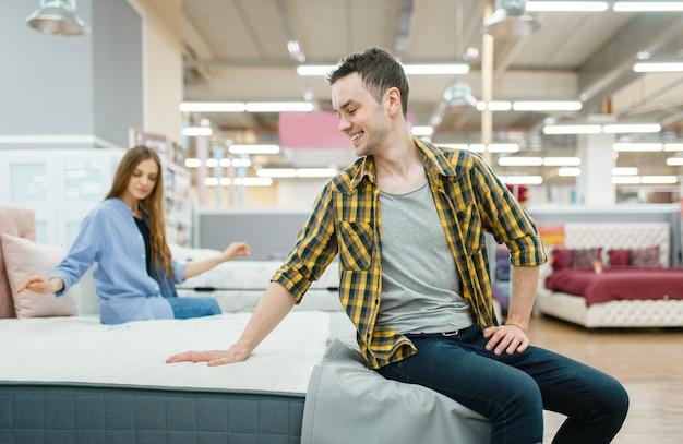 La giovane coppia d'amore controlla il materasso nello showroom del negozio di mobili. uomo e donna in cerca di campioni per la camera da letto in negozio, marito e moglie acquistano beni per interni domestici moderni