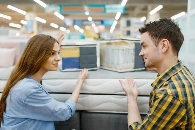 Giovani coppie di amore che scelgono il materasso per il letto nello showroom del negozio di mobili. uomo e donna in cerca di campioni per la camera da letto in negozio, marito e moglie acquistano beni per interni domestici moderni