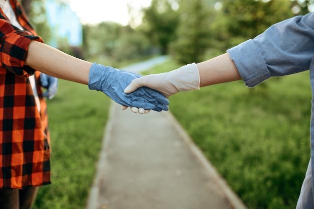 Coppia giovane amore in guanti passeggiate nel parco, quarantena. incontro romantico durante l'epidemia, assistenza sanitaria e protezione, stile di vita pandemico