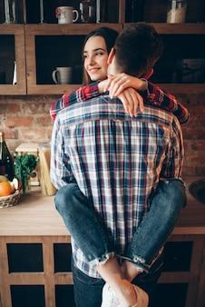 Giovani abbracci delle coppie di amore sulla cucina. uomo e donna si abbracciano, famiglia felice prima di cucinare una cena romantica