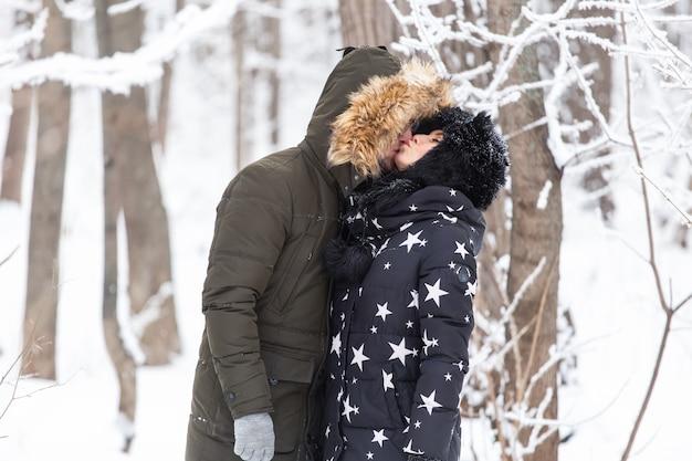 Giovane coppia d'amore che si bacia in un parco innevato