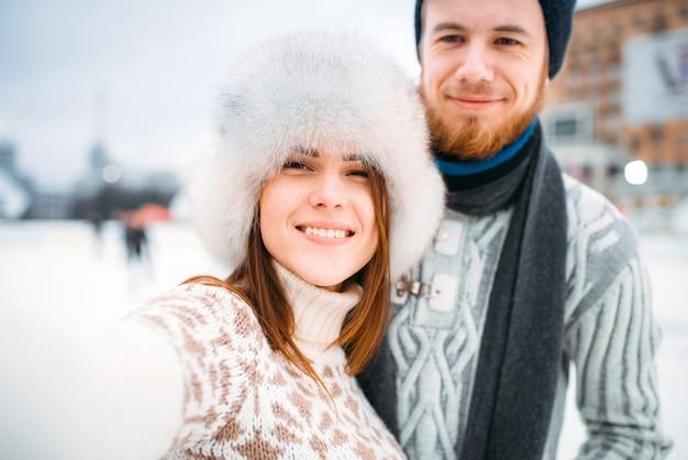 Coppia giovane amore, selfie sulla pista di pattinaggio. pattinaggio invernale all'aria aperta, tempo libero attivo, pattini uomo e donna insieme