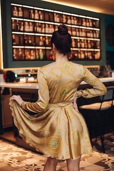 La giovane donna caucasica adorabile con capelli scuri in vestito d'argento e scarpe posa per la macchina fotografica e mostra il suo nuovo vestito