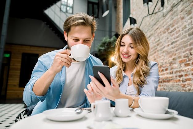 Giovani coppie adorabili che navigano sul web e che esaminano le foto sul telefono cellulare. in un caffè, l'hotel è una sala d'aspetto.