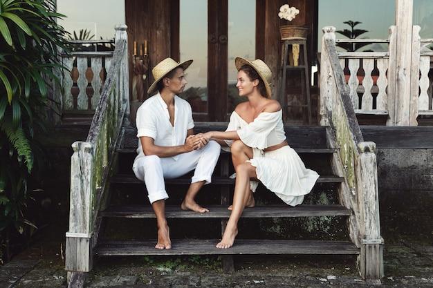 Giovane coppia adorabile che indossa abiti naturali è seduta sulle scale del portico