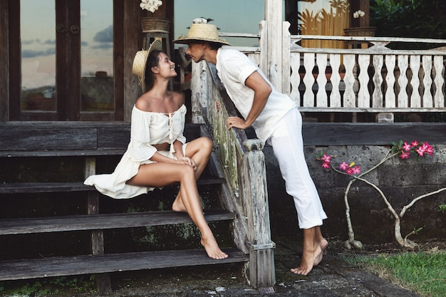 Giovane coppia adorabile che indossa abiti naturali seduti sotto il portico della loro casa
