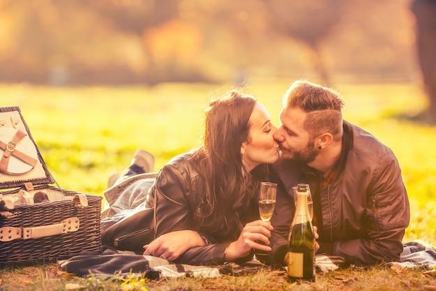 Giovani adorabili amanti delle coppie felici fanno un picnic nel parco autunnale coppia felice che si bacia nel parco autunnale