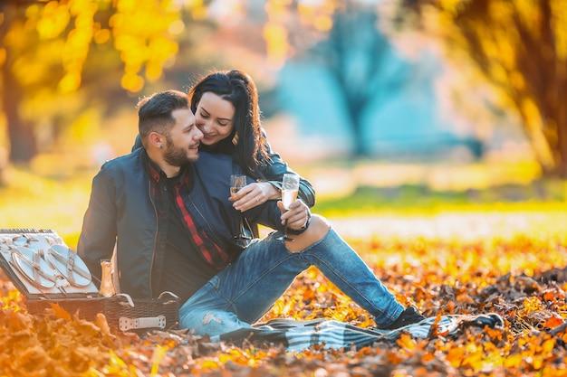 Giovani adorabili amanti delle coppie felici fanno un picnic nel parco autunnale coppia felice con champagne