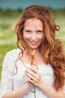 La giovane donna sorridente adorabile si meraviglia sul fiore, strappando i petali