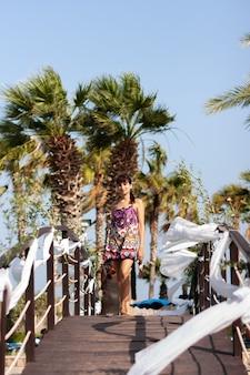 Giovane donna adorabile che posa sul ponte sopra la piscina al resort mediterraneo in una bella giornata di sole estivo