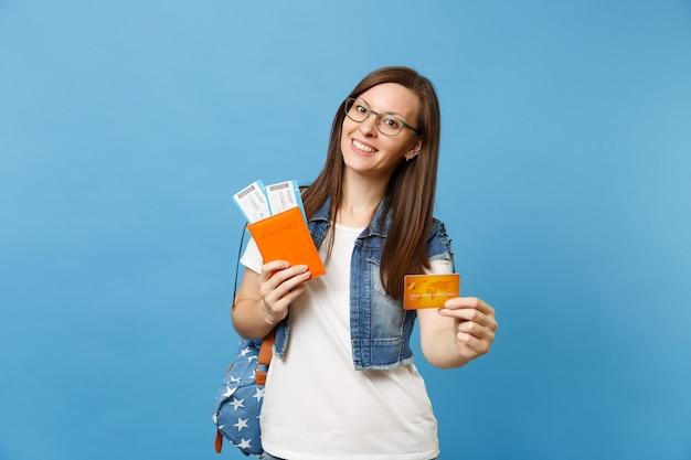 Giovane bella studentessa in bicchieri con zaino in possesso di passaporto, biglietti per la carta d'imbarco, carta di credito isolata su sfondo blu. istruzione in college universitario all'estero. concetto di volo di viaggio aereo.