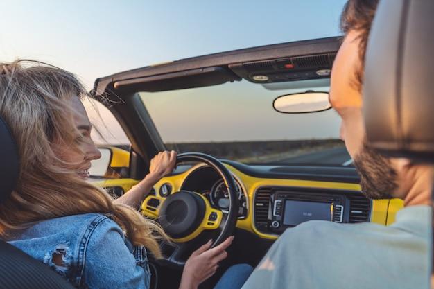 I giovani innamorati che viaggiano in macchina insieme