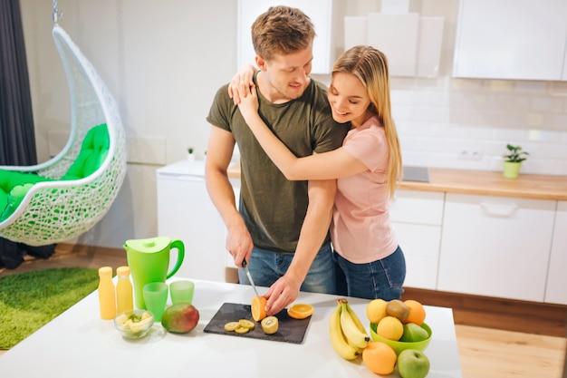 Giovani coppie amorose che cucinano frutta dolce organica per il succo al tavolo bianco