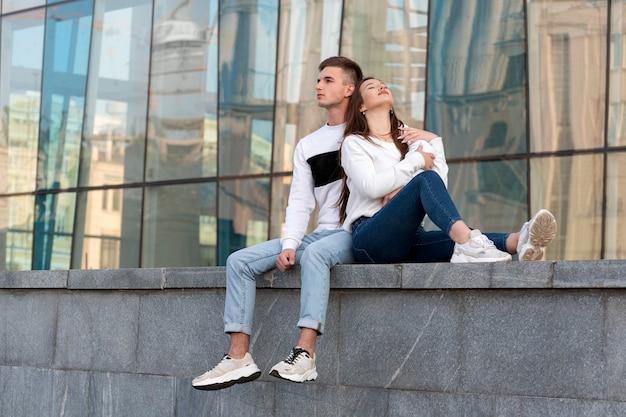 Giovani coppie amorose che riposano all'interno della città. la ragazza si appoggiò alla spalla del ragazzo. amore studentesco, romantico