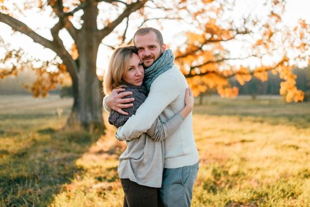 Giovani coppie amorose che abbracciano nel campo di autunno al tramonto
