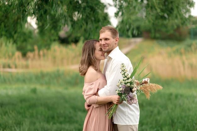 Giovani coppie amorose che abbracciano e che ballano sull'erba verde sul prato inglese