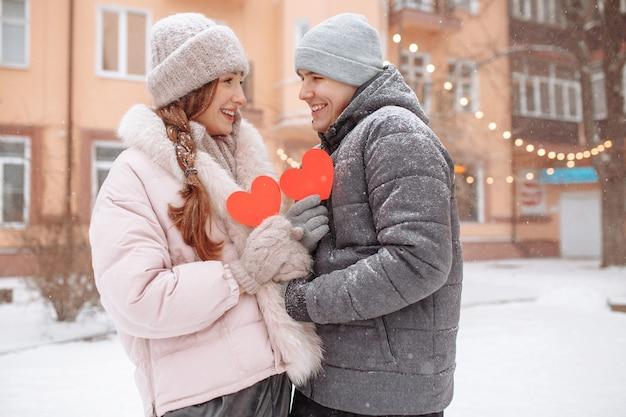 Giovani coppie amorose fuori in una giornata invernale che tengono i cuori di carta rossa nelle loro mani che provano gioia e amore. uomo e donna romantici festeggiano il giorno di san valentino sotto la neve in un parco.