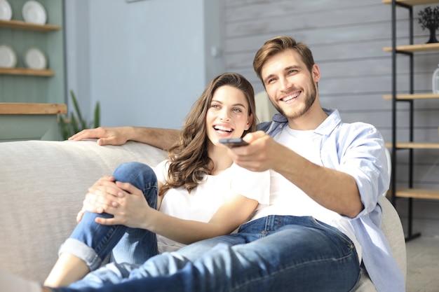 Giovani coppie amorose sul divano di casa a guardare la tv e ridere.