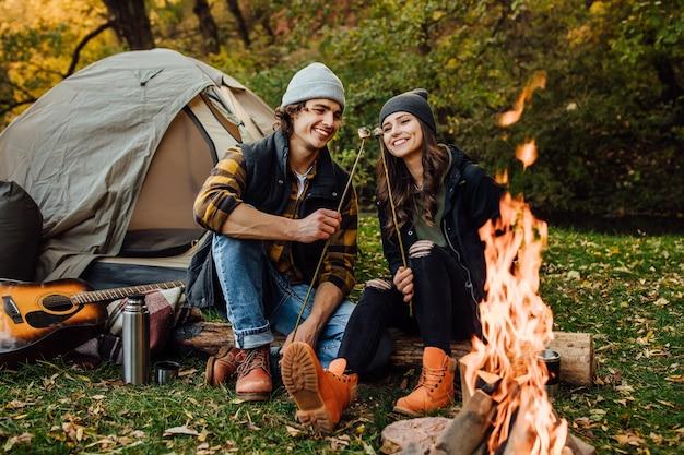 Giovani coppie amorose di turisti che si rilassano vicino al fuoco nella natura