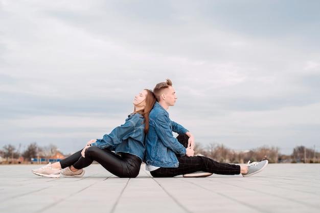 Giovani coppie amorose che indossano jeans seduti schiena contro schiena in strada trascorrere del tempo insieme
