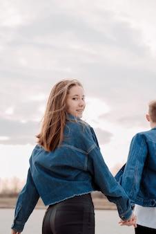 Giovani coppie amorose che indossano jeans che trascorrono del tempo insieme nel parco divertendosi, donna che si tiene per mano con il suo ragazzo che guarda indietro