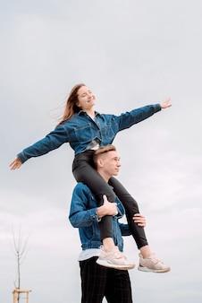 Giovani coppie amorose che indossano jeans che trascorrono del tempo insieme nel parco divertendosi