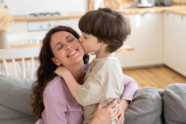 Giovane famiglia amorevole insieme ragazzo carino che dà un bacio tenero alla mummia felice esprime amore e cura