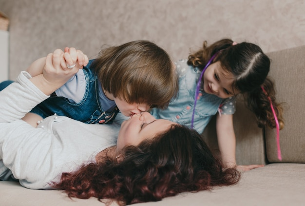 La giovane mamma amorevole e la bambina si baciano mentre giocano sdraiati sul divano. il concetto di felicità familiare