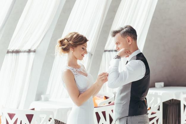 Giovani sposi innamorati che abbracciano e si baciano in un bellissimo ristorante